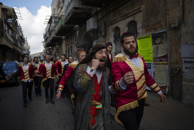 Ultra-Orthodox Jews celebrate after drinking alcohol during the Jewish holiday of Purim, in the Mea Shearim neighborhood of Jerusalem, Sunday, Feb. 28, 2021. Purim commemorates the Jews' salvation from genocide in ancient Persia, as recounted in the biblical Book of Esther. (AP Photo/Oded Balilty)