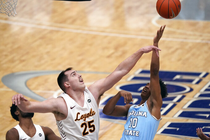 Loyola of Chicago's Cameron Krutwig (25) knocks the ball away from Indiana State's Julian Larry (10) during the first half of an NCAA college basketball game in the semifinal round of the Missouri Valley Conference men's tournament Saturday, March 6, 2021, in St. Louis. (AP Photo/Jeff Roberson)