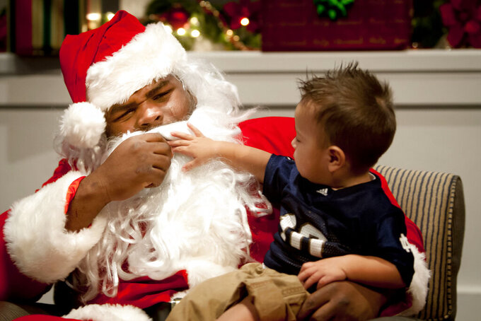 FILE - In this Thursday, Nov. 29, 2012, file photo, Gabreal Rico, 1, takes a tug at Louis Nix III's beard as the Notre Dame football nose guard plays the part of Santa Claus during Silent Night Silent Auction, an annual fundraiser held by Notre Dame's Pasquerilla East dormitory benefiting the American Cancer Society's Relay for Life at Notre Dame's LaFortune Student Center in South Bend, Ind. Nix's mother, Stephanie Wingfield, says authorities told her that her son had died but they were unable to give her more information about his death. The Jacksonville Sheriff's Office said in a tweet Saturday, Feb. 27, 2021, that Nix was located, but didn't give any other details.  (James Brosher/South Bend Tribune via AP, File)