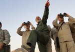 FILE - This file photo provided on Friday Oct. 20, 2017 by the government-controlled Syrian Central Military Media, shows Iran's army chief of staff Maj. Gen. Mohammad Bagheri, left looking into binoculars, and other senior officers from the Iranian military,  as they visit a front line in the northern province of Aleppo, Syria. As Syrian troops and their allies push toward final victory and the battle against Islamic State militants draws to an end, new fronts are opening up, threatening an even broader confrontation. The U.S., Israel and Turkey all have deepened their involvement, seeking to protect their interests in the new Syria order. (Syrian Central Military Media, via AP, File)