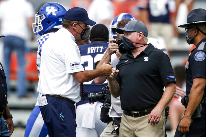 Auburn head coach Gus Malzahn, left, and Kentucky head coach Mark Stoops fist bump after an NCAA college football game on Saturday, Sept. 26, 2020, in Auburn, Alabama. Auburn won 29-13. (AP Photo/Butch Dill)