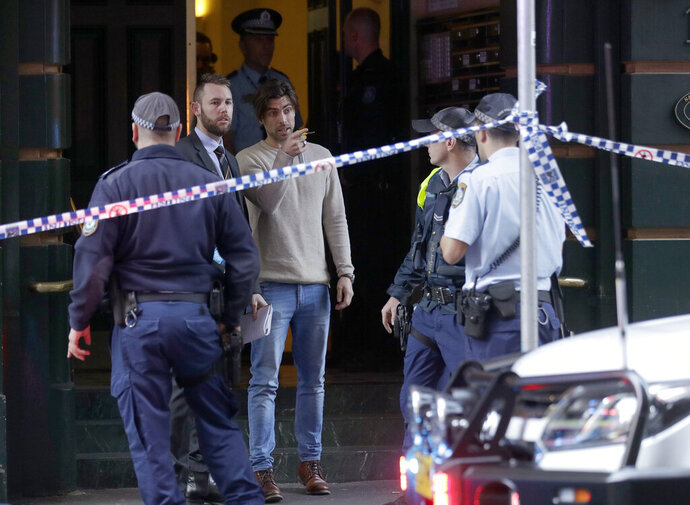 A man, center, points as he assists police at a building where a person has been found deceased after a man attempted to stab multiple people in Sydney, Australia, Tuesday, Aug. 13, 2019. Police and witnesses say a knife-wielding man yelling