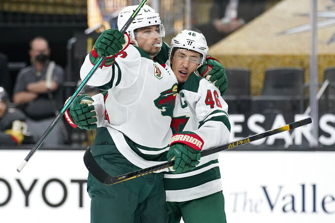 Minnesota Wild left wing Kevin Fiala, left, celebrates after Minnesota Wild defenseman Jared Spurgeon (46) scored against the Vegas Golden Knights during the third period of an NHL hockey game Thursday, April 1, 2021, in Las Vegas. (AP Photo/John Locher)