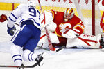 Calgary Flames goalie David Rittich, right, makes a save as Toronto Maple Leafs' Joe Thornton drives to the net during the second period of an NHL hockey game Sunday, April 4, 2021, in Calgary, Alberta. (Larry MacDougal/The Canadian Press via AP)
