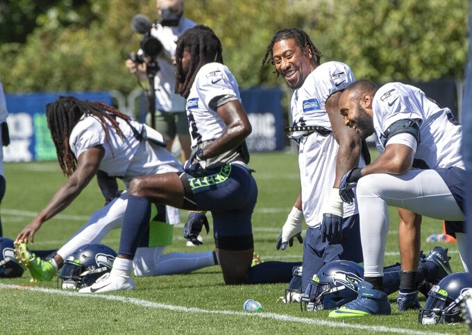 Bruce Irvin and K.J. Wright (at right) are in good spirits during training camp Tuesday, Aug. 25, 2020, in Renton, Wash. (Dean Rutz/The Seattle Times via AP, Pool)
