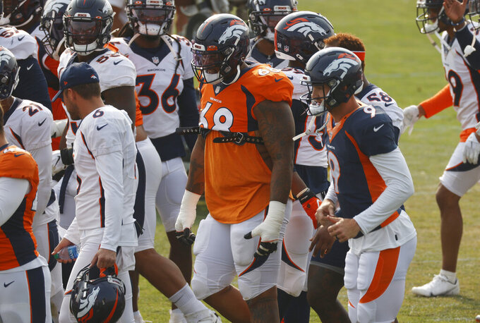 Denver Broncos offensive tackle Elijah Wilkinson, center, joins teammates to takes part in drills during an NFL football training practice Friday, Aug. 21, 2020, in Englewood, Colo. (AP Photo/David Zalubowski)