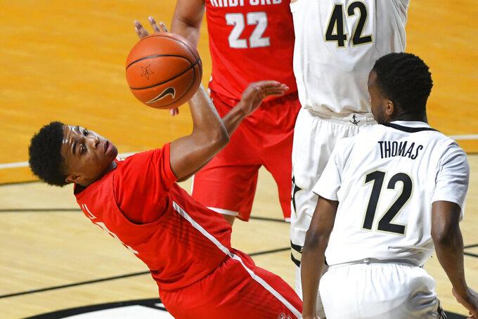 Radford guard Fah' Mir Ali, left, has a shot rejected during the second half of an NCAA college basketball game against Vanderbilt, Saturday, Dec. 19, 2020, in Nashville, Tenn. Vanderbilt won 59-50. (AP Photo/John Amis)