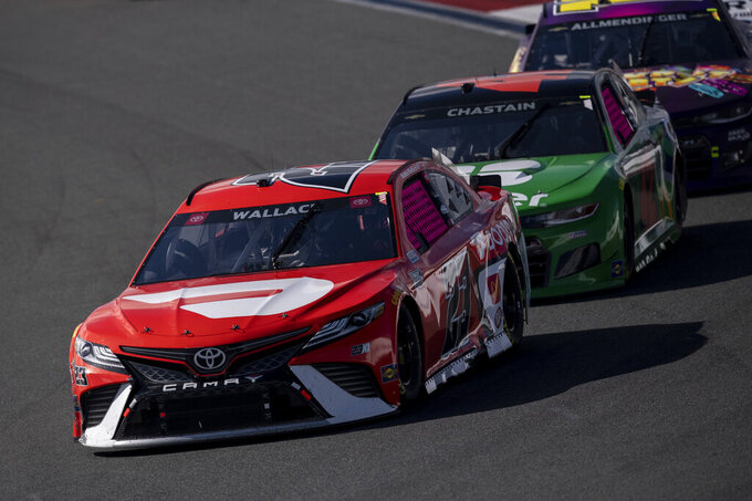 Bubba Wallace (23) leads a pack of cars during a NASCAR Cup Series auto racing race at Charlotte Motor Speedway, Monday, Oct. 11, 2021, in Concord, N.C. (AP Photo/Matt Kelley)