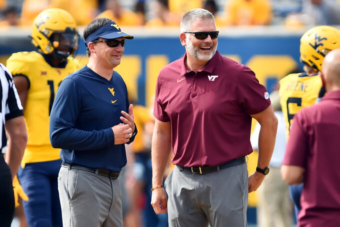 West Virginia head coach Neal Brown,left, talks with Virginia Tech head coach Justin Fuente before an NCAA college football game in Morgantown, W.Va., Saturday, Sept. 18, 2021. (AP Photo/William Wotring)