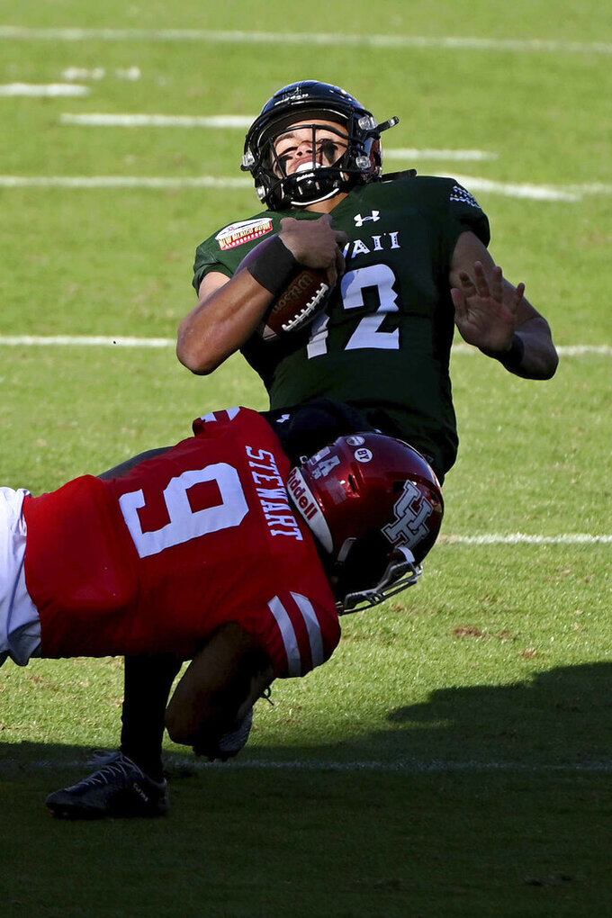 Hawaii quarterback Chevan Cordeiro (12) is tackled by Houston linebacker JoVanni Stewart (9) in the first quarter of the New Mexico Bowl NCAA college football game in Frisco, Texas, Thursday, Dec. 24, 2020. (AP Photo/Matt Strasen)