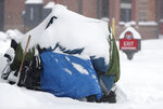 Snow covers a tarpaulin pulled over a shopping cart being used by a homeless person as a storm packing snow and high winds sweeps in over the region Tuesday, Nov. 26, 2019, in Denver. Stores, schools and government offices were closed or curtailed their hours while on another front, Thanksgiving Day travellers were forced to wrestle with snow-packed roads and flight delays or cancellations throughout the intermountain West. (AP Photo/David Zalubowski)