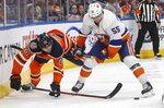 New York Islanders' Johnny Boychuk (55) and Edmonton Oilers' Leon Draisaitl (29) battle for the puck during second-period NHL hockey game action in Edmonton, Alberta, Thursday, Feb. 21, 2019. (Jason Franson/The Canadian Press via AP)