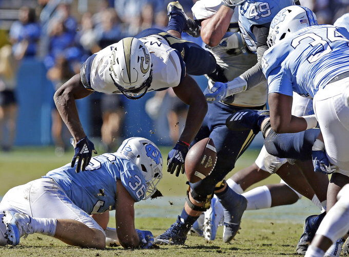 Georgia Tech's Jordan Mason (24) fumbles after a hit by North Carolina's Cole Holcomb (36) during the second half of an NCAA college football game in Chapel Hill, N.C., Saturday, Nov. 3, 2018. UNC recovered the ball. Georgia Tech won 38-28. (AP Photo/Gerry Broome)