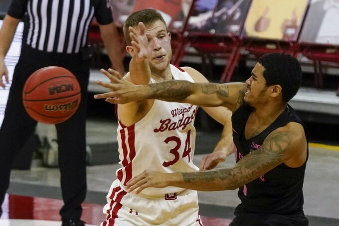 Penn State's Sam Sessoms passes around Wisconsin's Brad Davison during the first half of an NCAA college basketball game Tuesday, Feb. 2, 2021, in Madison, Wis. (AP Photo/Morry Gash)