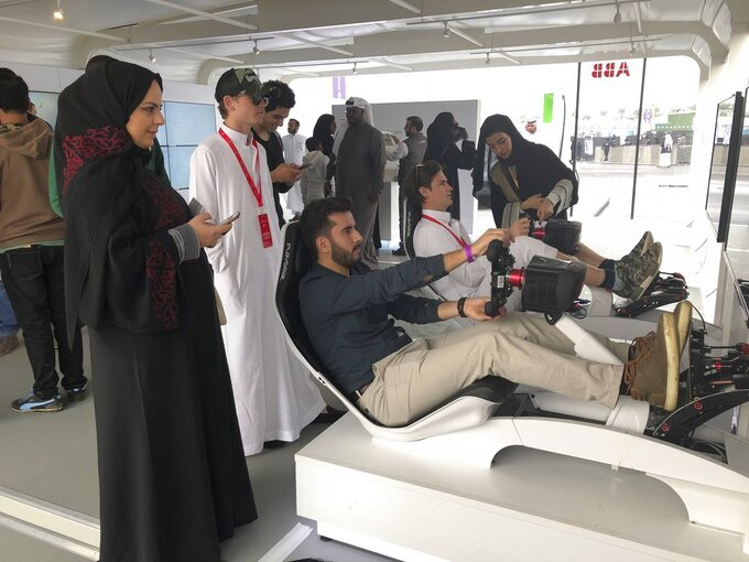 Hostesses in black robes and headscarves give instructions to foreign visitors trying out a simulator at a Formula-E race on the outskirts of Riyadh, Saudi Arabia on Saturday, Dec. 15, 2018. Men and women mingled freely during the event, a scene that would have been unthinkable in the ultra-conservative kingdom until recently. (AP Photo/Karin Laub)