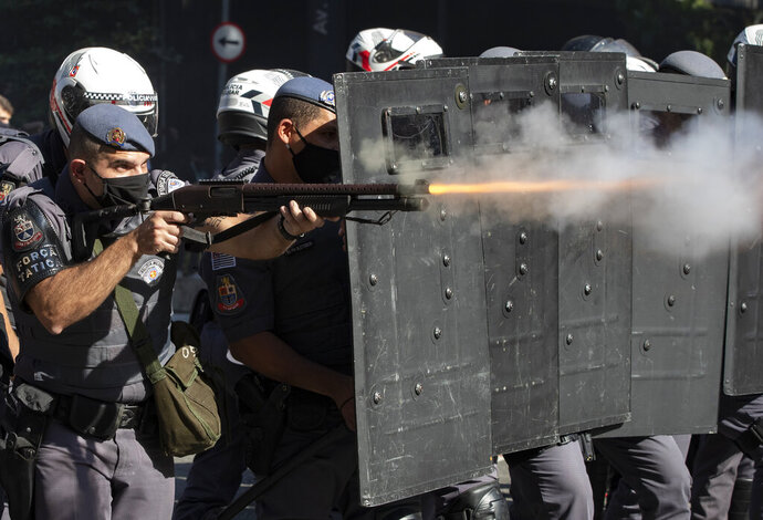 Police clash with anti-government demonstrators in Sao Paulo, Brazil, Sunday, May 31, 2020. Police used tear gas to disperse anti-government protesters in Brazil's largest city as they began to clash with small groups loyal to President Jair Bolsonaro. (AP Photo/Andre Penner)