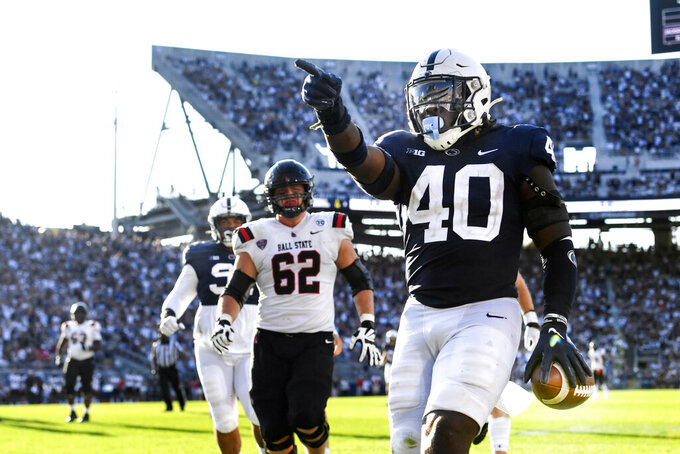 Penn State linebacker Jesse Luketa (40) celebrates after intercepting Ball State quarterback Drew Plitt (9) and returning it for a touchdown in the third quarter of an NCAA college football game in State College, Pa., on Saturday, Sept. 11, 2021. Penn State defeated Ball State 44-13. (AP Photo/Barry Reeger)