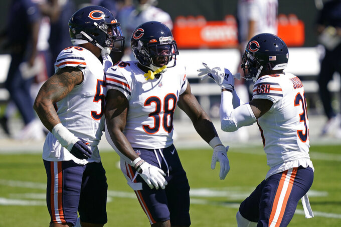 Chicago Bears strong safety Tashaun Gipson (38) is congratulated by linebacker Josh Woods (55) and free safety Eddie Jackson (39) after Gip[son's interception against the Carolina Panthers during the first half of an NFL football game in Charlotte, N.C., Sunday, Oct. 18, 2020. (AP Photo/Brian Blanco)