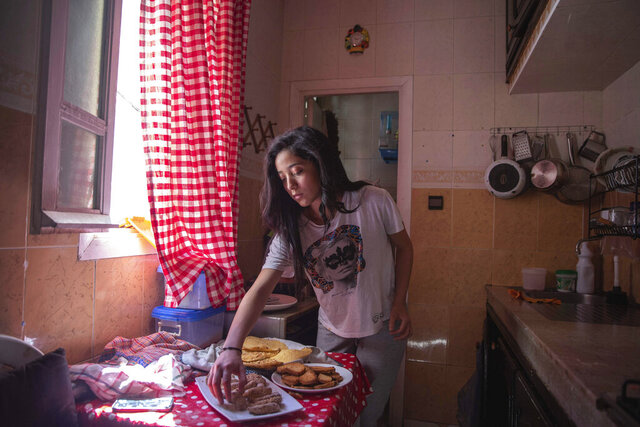 Fadila Lahta prepares a plate of Moroccan sweets in her aunt's home as they spend Eid in lockdown due to the Coronavirus pandemic, in Sale, Morocco, Sunday, May 24, 2020. (AP Photo/Mosa'ab Elshamy)