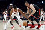 Portland Trail Blazers center Hassan Whiteside, left, and Toronto Raptors center Marc Gasol reach for a loose ball during the first half of an NBA basketball game in Portland, Ore., Wednesday, Nov. 13, 2019. (AP Photo/Craig Mitchelldyer)