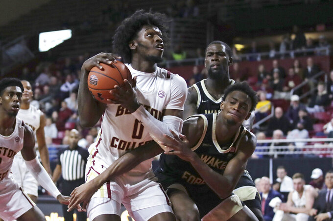 Wake Forest forward Isaiah Mucius, right, tries to block Boston College forward CJ Felder (0) during the second half of an NCAA college basketball game in Boston, Wednesday, Nov. 6, 2019. (AP Photo/Charles Krupa)