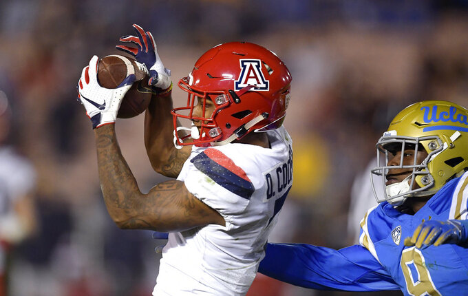 Arizona wide receiver Devaughn Cooper, left, makes a catch as UCLA defensive back Elijah Gates defends during the second half of an NCAA college football game Saturday, Oct. 20, 2018, in Pasadena, Calif. UCLA won 31-30. (AP Photo/Mark J. Terrill)