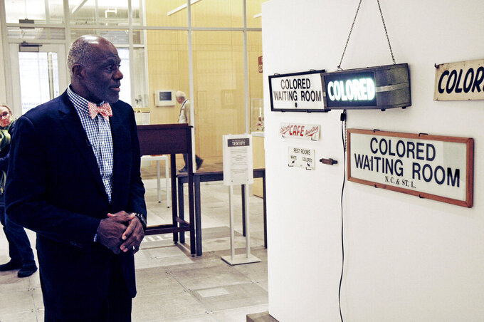 File-In this Jan. 11, 2018 file photo, Alan Page, NFL Hall of Famer and retired Minnesota Supreme Court justice, looks at a display which is among the artifacts of slavery and segregation collected by Page and his wife, Diane Sims Page.  Page has counted art collection among his many life pursuits, and the former Vikings star has two of his prized pieces up for sale through a New York auction house, each valued at more than $200,000. (AP Photo/Steve Karnowski, File)