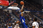 Tulsa's Elijah Joiner, top, dunks  against Connecticut's Akok Akok (23) in the first half of an NCAA college basketball game, Sunday, Jan. 26, 2020, in Hartford, Conn. (AP Photo/Jessica Hill)