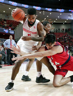Houston guard Corey Davis Jr. (5) gets control of a loose rebound over New Jersey Institute of Technology forward Mohamed Bendary (34)during the first half of an NCAA college basketball game Saturday, Dec. 29, 2018, in Houston. (AP Photo/Michael Wyke)
