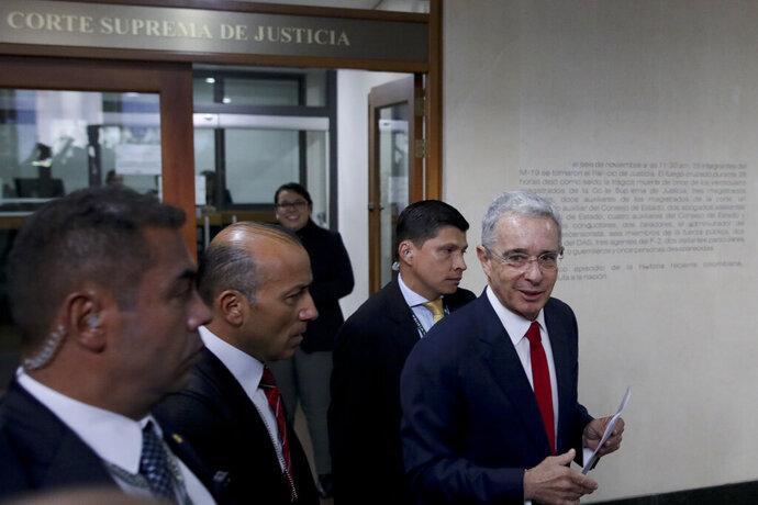 Colombia's former President Alvaro Uribe, right, arrives to the Supreme Court for questioning in a case involving witness tampering, in Bogota, Colombia, Tuesday, Oct. 8, 2019. A magistrate was expected to ask Uribe behind closed doors about accusations that, through a lawyer, he tried to influence and even bribe members of a paramilitary group who had damaging information against him. (AP Photo/Ivan Valencia)
