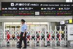 A worker walks past closed ticket gates at a station in Hiroshima, western Japan Thursday, Aug. 15, 2019. A powerful typhoon is lashing southwestern Japan with massive rain and strong winds, paralyzing traffic during Japan's Buddhist holiday week. (Shingo Nishizume/Kyodo News via AP)