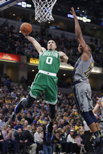 Boston Celtics forward Jayson Tatum (0) goes up for a dunk over Indiana Pacers forward Thaddeus Young (21) during the second half of an NBA basketball game in Indianapolis, Friday, April 5, 2019. (AP Photo/Michael Conroy)