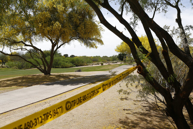 FILE - In this April 10, 2018, file photo, police tape cordon off an area near the site of a plane crash that killed several people in Scottsdale, Ariz. A federal agency's findings in the investigation of a 2018 plane crash in Arizona that killed all six people aboard is expected to affect at least two lawsuits filed in Nevada against the estates of the dead pilots, the aircraft owner and casino giant MGM Resorts International. The pilot radioed during the ill-fated takeoff from Scottsdale Airport that the flight was