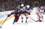 Columbus Blue Jackets' Sonny Milano, left, controls the puck in front of New York Rangers' Marc Staal, center, and Brett Howden during the second period of an NHL hockey game Friday, Feb. 14, 2020, in Columbus, Ohio. (AP Photo/Jay LaPrete)