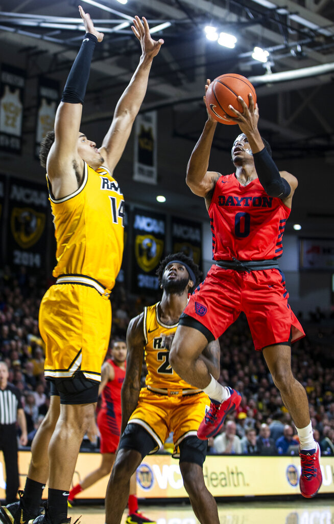 Dayton guard Rodney Chatman (0) goes up for a shot as VCU forward Marcus Santos-Silva (14) plays defense during the first half of an NCAA college basketball game, Tuesday, Feb. 18, 2020, in Richmond, Va. (AP Photo/Zach Gibson)