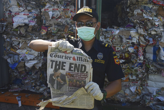Indonesian custom officers show off the front of a foreign newspaper amoung waste found in a container at the Tanjung Perak port in Surabaya, East Java, Indonesia, Tuesday, July 9, 2019. Indonesia is sending dozens of containers of imported waste back to Western nations after finding it was contaminated with used diapers, plastic and other materials, adding to a growing backlash in Southeast Asia against being a dumping ground for the developed world's rubbish. (AP Photo)