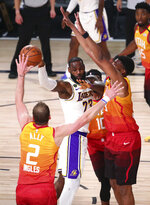 Los Angeles Lakers forward LeBron James (23) passes the ball away from Utah Jazz players, from left, Joe Ingles (2) , Mike Conley (10) and Tony Bradley (13) during the first half of an NBA basketball game Monday, Aug. 3, 2020, in Lake Buena Vista, Fla. (Kim Klement/Pool Photo via AP)