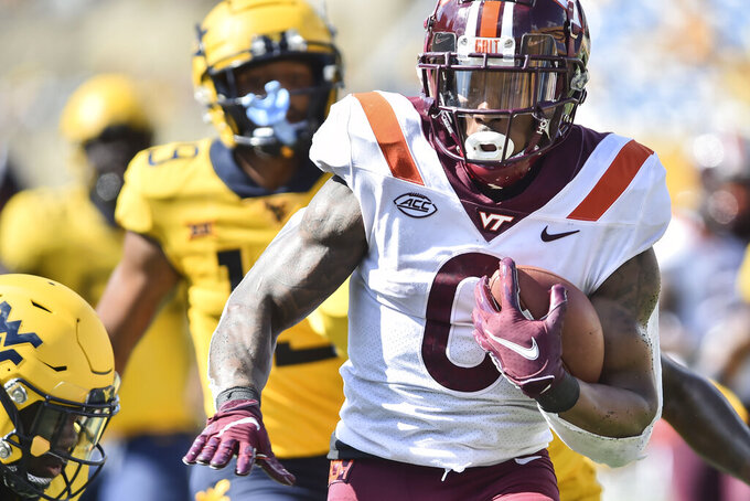 Virginia Tech running back Jalen Holston (0) rushes in for a touchdown against West Virginia during the second half of an NCAA college football game in Morgantown, W.Va., Saturday, Sep. 18, 2021. (AP Photo/William Wotring)