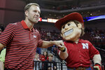 In this Wednesday, Oct. 30, 2019 photo, Nebraska coach Fred Hoiberg is greeted by mascot Herbie Husker, before an NCAA college basketball exhibition game against Doane University in Lincoln, Neb. Hoiberg knows the track record of Nebraska basketball coaches is not good. He wanted the job anyway. He takes over a program that has not won a conference championship in 70 years or ever won a game in the NCAA Tournament. He says a sold-out arena and top-notch facilities can trump the program's lack of tradition. (AP Photo/Nati Harnik)