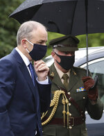 Prime Minster of Ireland Michael Martin arrives to attends the former Northern Ireland lawmaker and Nobel Peace Prize winner John Hume's funeral Mass at St Eugene's Cathedral in Londonderry, Northern Ireland, Wednesday, Aug. 5, 2020. Hume was co-recipient of the 1998 Nobel Peace Prize with fellow Northern Ireland lawmaker David Trimble, for his work in the Peace Process in Northern Ireland. Martin and his aide are wearing masks due to the Coronavirus outbreak. (AP Photo/Peter Morrison)