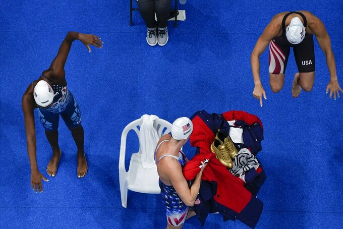 Catie de Loof, Allison Schmidt and Natalie Hinds of the United States get ready to swim in a preliminary round of the women's 4x100m freestyle relay at the 2020 Summer Olympics, Saturday, July 24, 2021, in Tokyo, Japan. (AP Photo/Morry Gash)