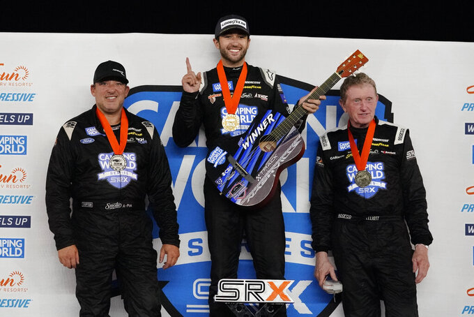 Chase Elliott, center, holds his winner's guitar after winning the SRX Series auto race Saturday, July 17, 2021, in Nashville, Tenn. Tony Stewart, left, finished second, and Bill Elliott, right, finished third. (AP Photo/Mark Humphrey)
