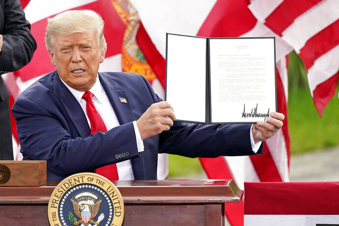 President Donald Trump holds a signed memorandum to expand the offshore drilling moratorium to Florida's Atlantic coast, Georgia and South Carolina after speaking at the Jupiter Inlet Lighthouse and Museum Tuesday, Sept. 8, 2020, in Jupiter, Fla. (AP Photo/John Raoux)
