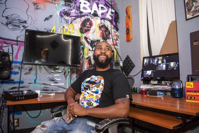 Co-owner of 131 Collective Studios Trevon Tatum sits for a portrait on Monday, Oct. 12, 2020 in Battle Creek, Mich.   Tatum, with older brother Trenel Tatum and their friend, Derek Freeman, own 131 Collective Studios in Battle Creek. The group is leasing space at the site in the city's light industrial district and running at least eight separate business offerings under the 131 Collective Studios umbrella.  (Alyssa Keown/Battle Creek Enquirer via AP)