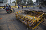 People ride past police barricades damaged by protestors in Gauhati, India, Thursday, Dec. 12, 2019. Police arrested dozens of people and enforced curfew on Thursday in several districts in India's northeastern Assam state where thousands protested legislation granting citizenship to non-Muslims who migrated from neighboring countries. (AP Photo/Anupam Nath)
