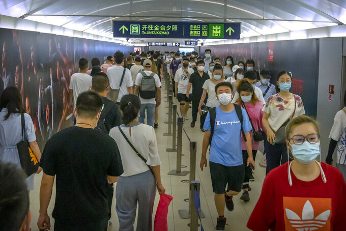 People wearing face masks to help protect against COVID-19 walk through a subway station during the morning rush hour in Beijing, Wednesday, Aug. 4, 2021. China's worst coronavirus outbreak since the start of the pandemic a year and a half ago escalated Wednesday with dozens more cases around the country, the sealing-off of one city and the punishment of its local leaders. (AP Photo/Mark Schiefelbein)