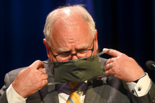 Minnesota Gov. Tim Walz put his face mask at the conclusion of a press conference Thursday, July 30, 2020 announcing the learning plan for Minnesota schools for the upcoming 2020-21 school year.  (Aaron Lavinsky/Star Tribune via AP, Pool)