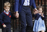FILE - In this Monday, April 23, 2018 file photo, Britain's Prince William holds the hands of Prince George and Princess Charlotte at the Lindo wing at St Mary's Hospital in London.  Kensington Palace said Thursday Aug. 29, 2019, that the four-year-old daughter of Prince William and Catherine, Duchess of Cambridge, Princess Charlotte will attend her first day of school upcoming Sept. 5. Charlotte and six-year-old Prince George will be students at Thomas's Battersea school in London. (AP Photo/Kirsty Wigglesworth, FILE)