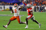 Clemson running back Travis Etienne, left, runs for a touchdown past Ohio State safety Jordan Fuller during the first half of the Fiesta Bowl NCAA college football playoff semifinal Saturday, Dec. 28, 2019, in Glendale, Ariz. (AP Photo/Rick Scuteri)