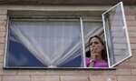 "Myriam Roncancio smokes a cigarette as she poses for a photo in her window during a nationwide stay-at-home order to slow the spread of the new coronavirus, in the Soacha borough of Bogota, Colombia, Tuesday, July 28, 2020. ""From one moment to the next, my life changed,"" says the 35-year-old mother of two, who is living with her parents after breaking up with her husband of 10 years. ""A 180-degree turn."" (AP Photo/Fernando Vergara)"